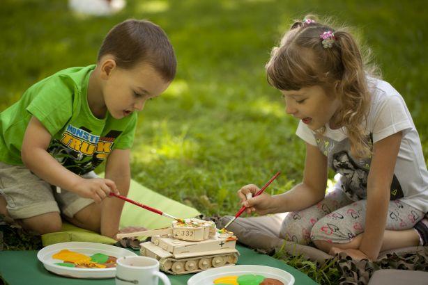Zdjęcie chłopca i dziewczynki, malujących model czołgu farbami.