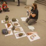 Edukatorka pokazuje obrazki z wyposażeniem żołnierza, przed nią leżą rozłożone karty i eksponaty.