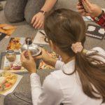 Dziewczynka ogląda manierkę, przed dziewczynką leżą fotografie z potrawami.