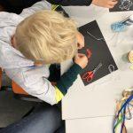 Chłopiec pochylony nad czarną kartką, wykonuje pracę plastyczną.