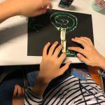Dłonie dziecka wyklejają drzewo z zielonego sznurka i patyczków.